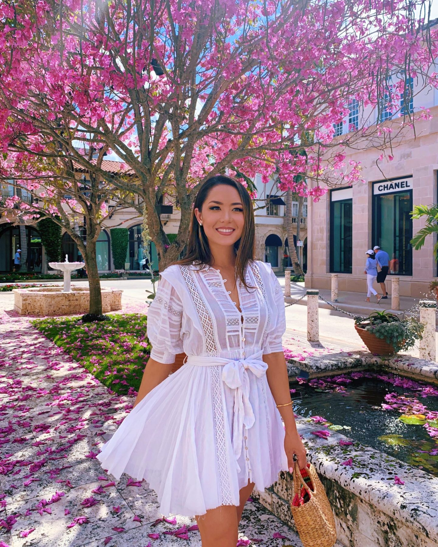 brunette in white dress with purple spring flowers in Palm Beach